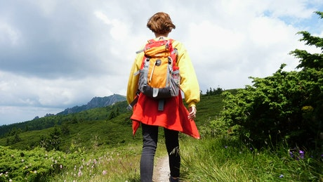 Girl with a backpack hiking in the hills