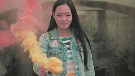 Girl with a smoke bomb near a bridge