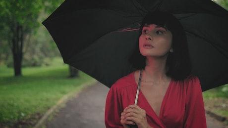 Girl with an umbrella walking through a park