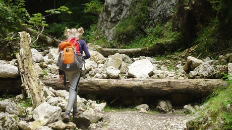 Girl with backpack walking through a rocky forest