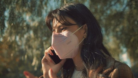 Girl with face mask talking on the cellphone
