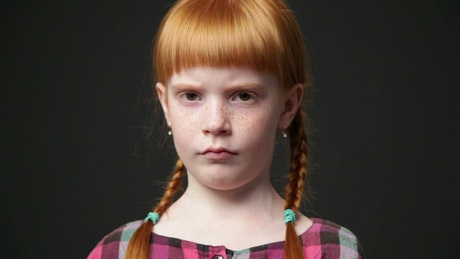 Girl with ginger hair frowning
