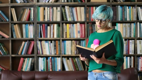 Girl with glasses reading a book in a library