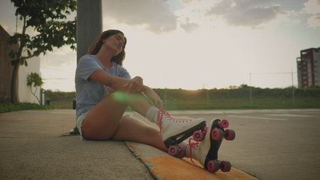 Girl with roller skates resting on the bench at sunset