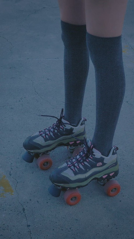 Girl with roller skates standing in the middle of a parking lot