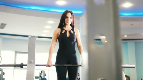 Girl working out in a gym with a dumbbell