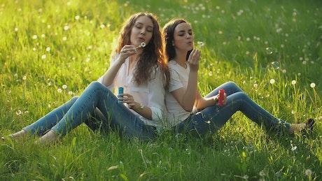 Girlfriends sitting in a meadow blowing bubbles