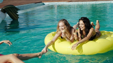 Girls in bikinis eat ice cream on pool floats