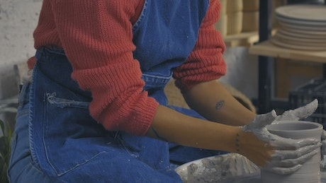 Girls making clay vases in a pottery class