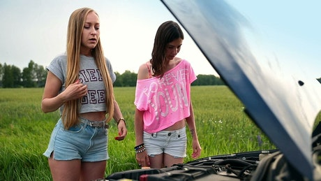 Girls on the side of a road with broken down car