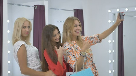 Girls take a selfie in a dressing room while shopping