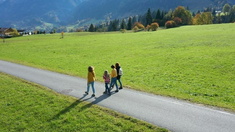 Girls walking on a road between grass fields