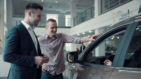 Giving the key to a new car owner