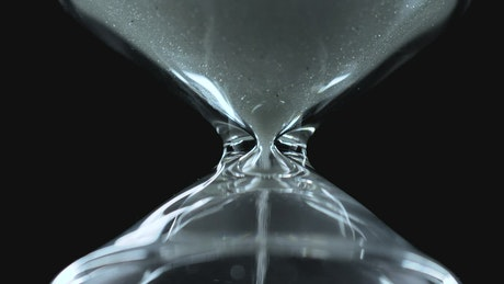 Glass hourglass close up on a black background