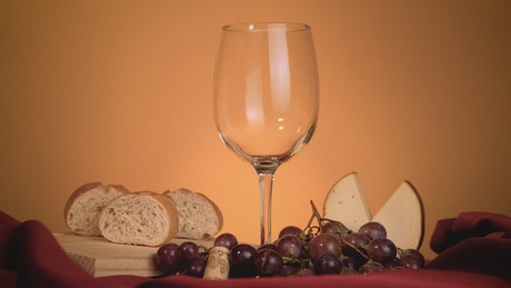 Glass of red wine surrounded by grapes, bread and cheese