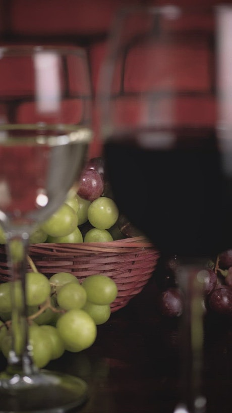 Glasses with red and white wine with a basket of grapes behind