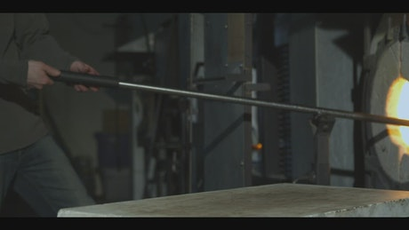 Glazier taking glass out of a furnace and shaping it