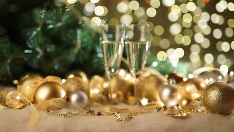 Gold holiday ornaments and champagne glasses on green bokeh
