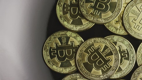 Golden bitcoins rotating on a black plate