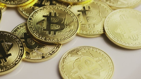 Golden physical bitcoins rotating on a surface