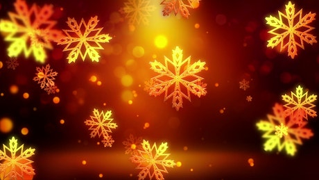 Golden snowflakes falling on red background.