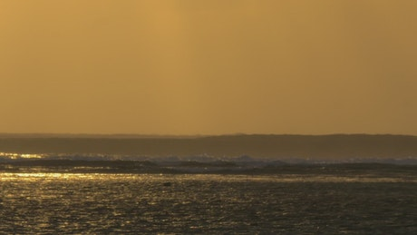 Golden sunset and tall waves