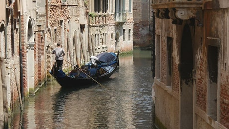 Gondola moving on a canal in Venice