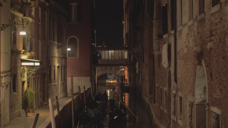 Gondolier heading down a river at night