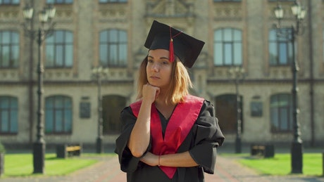 Graduate in cap and gown thinks about future