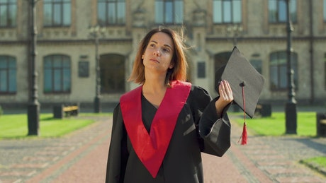 Graduate student in gown holding hat outside university