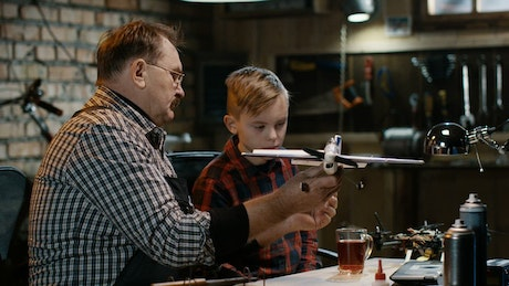 Grandfather and grandson repairing a toy plane