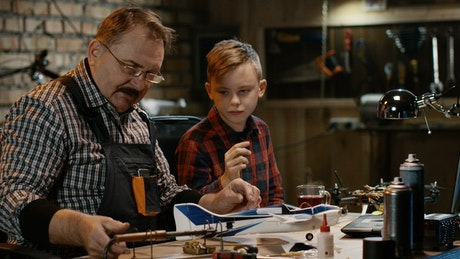 Grandfather and grandson repairing the toy plane