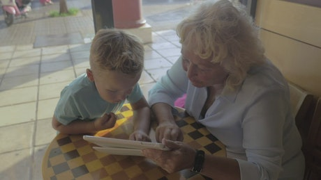 Grandmother and child using a tablet