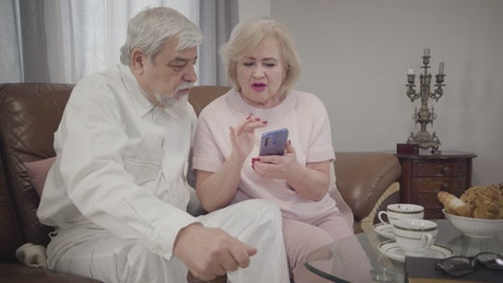 Grandmother teaches her husband how to use a phone