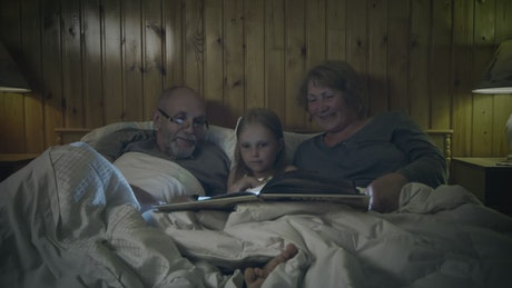 Grandparents reading a story to their grandchild