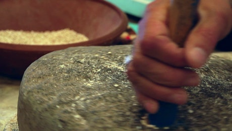 Grinding wheat with a rotating stone