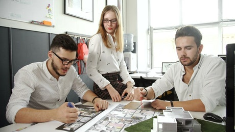Group of architects discussing a building model
