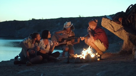 Group of friends singing around the campfire
