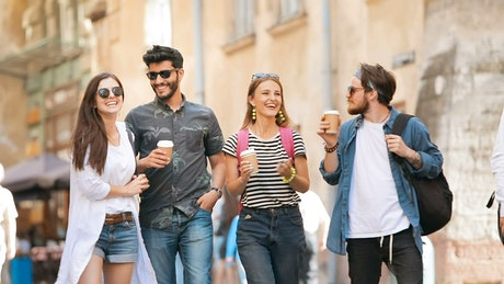 Group of friends walk on street with coffee