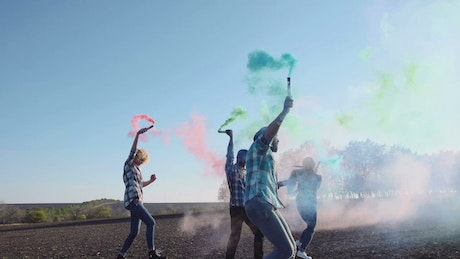 Group of friends with colored smoke grenades