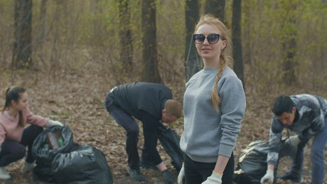 Group of people collecting garbage from the forest