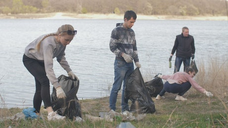 Group of volunteers cleaning up trash near a river