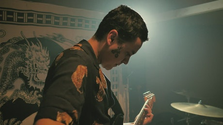 Guitarist playing electric guitar with his band