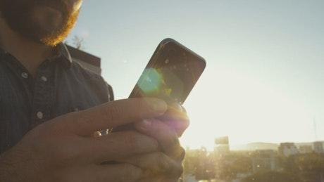 Guy texting at sunset