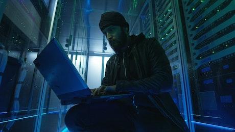 Hacker sitting on the ground of data center