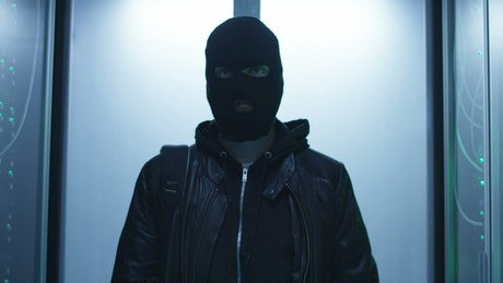 Hacker with face mask entering data center