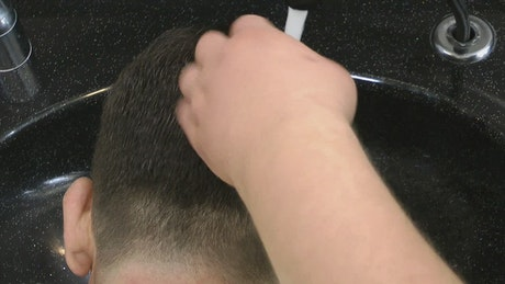 Hairdresser washing a client's hair