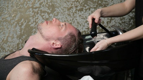 Hairdresser washing a mans hair
