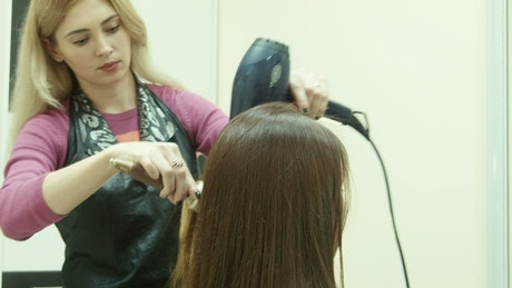 Hairstylist drying the hair of the client