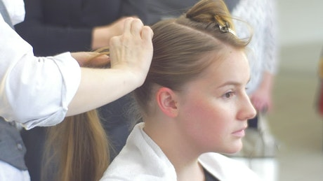 Hairstylist working on a blonde woman's hair
